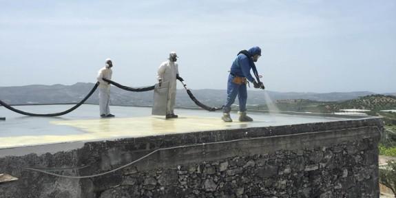 Volontari impermeabilizzano il tetto di un asilo